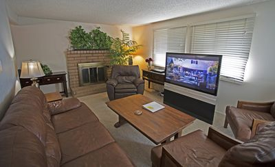 LIVING ROOM WITH ALL LEATHER FURNITURE, FIREPLACE AND WIDESCREEN TV.