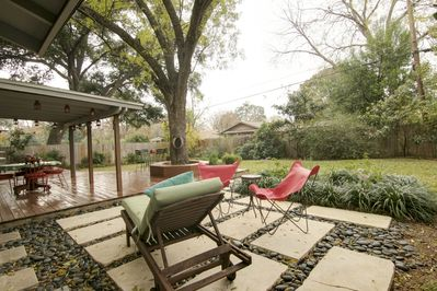 Backyard fully fenced with privacy fence, a covered deck and various forms of outdoor seating