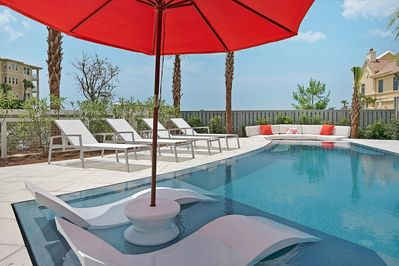 Infinity edge pool with tanning ledge loungers, fire pit & comfortable furniture