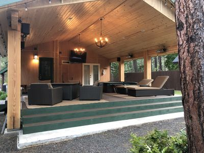 Brand new covered deck with fire table, hot tub, bar, and lounges.