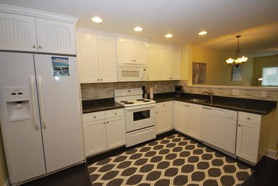 The fully equipped kitchen with granite counter tops, plates, silverware, etc.
