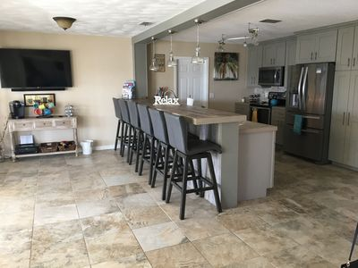 "Kitchen with high end appliances, bar w/seating for 6 and a 55"" tv."