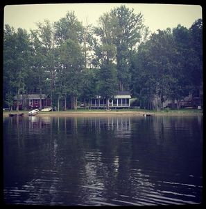 View of the cottage from the lake. It has the white roof and porch on the front.