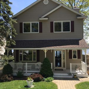 Front of home features covered porch and surrounded by beautiful garden
