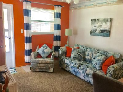 """Living room with 50"""" flat screen TV & free WI-FI. Air conditioned & ceiling fans"""