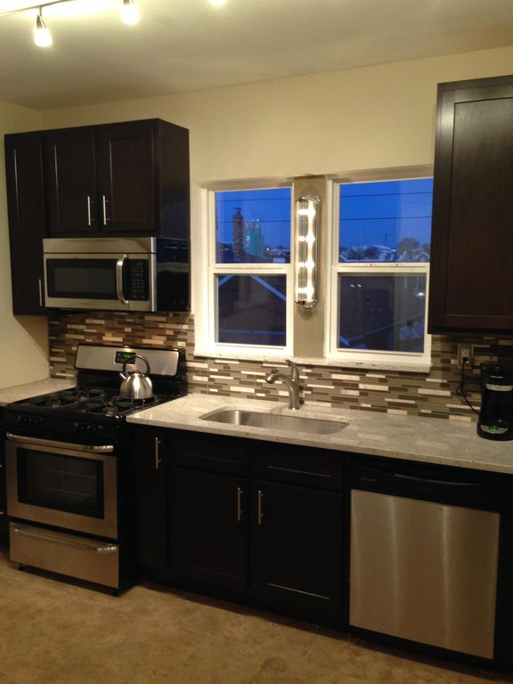 Gorgeous Kitchen With Dark Cabinets, Stainless Steel Appliances And Granite  Tops