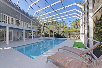 Pool area with four lounge chairs and two adirondack chairs