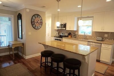 The renovated kitchen has a large island and 3 bar stools.