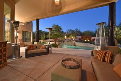 Outdoor covered living area with (4) patio heaters, bar top, and TV