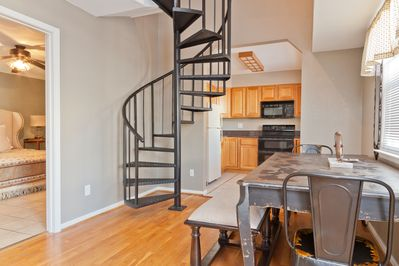 The kitchen, dining room, and stairway to the loft portion of the space.