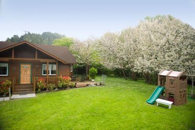 The beautiful, landscaped yard includes a swing-set and play house for children.