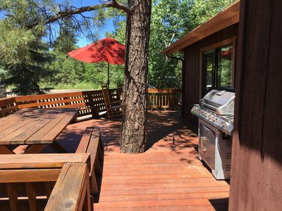 Huge side deck with table, ample bench seating and propane barbecue