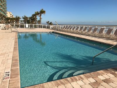 Large heated pool and hot tub sitting directly next to the beach
