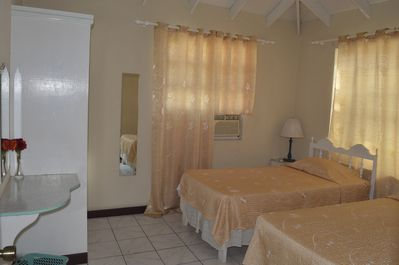 Air conditioned bedroom with 2 twin beds, en suite bath + beach front bay window