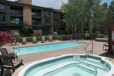 Pool and Hot Tub area with comfy sunbathing lounge furniture, flower baskets