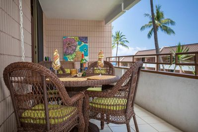 Wicker patio table and chairs with wine glasses on covered lanai