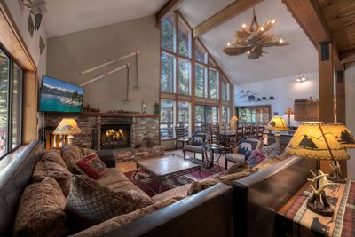 Open great room with floor to ceiling windows, fireplace, dining and big kitchen