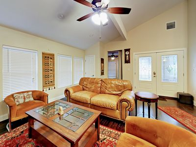 Living Room - Relax in the cozy living room, appointed with a sofa, armchairs, flat-screen TV, and ceiling fan.