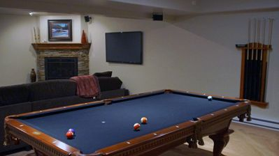 Rec room in basement with pool table and ping pong table top.