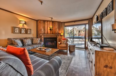 "Living Room with Comfortable Mountain Contemporary Furnishings, Wood Fireplace and 47"" Smart TV"