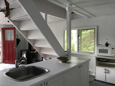 Stairs from kitchen to two bedrooms on the second floor of A-frame