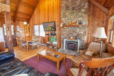 Laurel Chase Great Room with sofa by stone fireplace and large flat screen TV