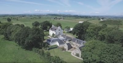 Aerial view of House and courtyard  looking out to sea and island of Arr