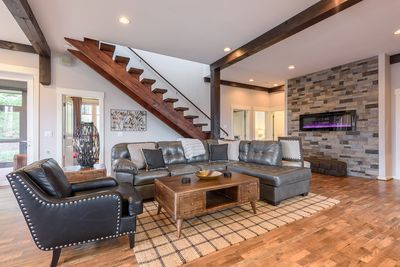 Designer Leather Furniture and Wall-Mounted Electric Fireplace in Living Room Note: The owner has installed an outer railing to make the staircase safer.
