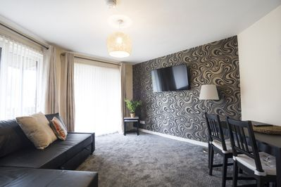 """Stylish lounge with feature wall and 50"""" smart TV"""