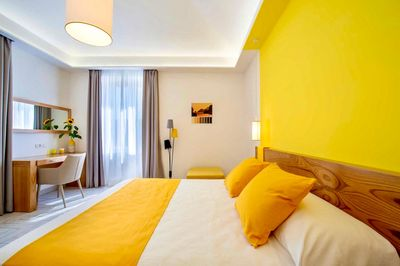 The bright yellow accents and the large windows make the space bright as light floods the room.