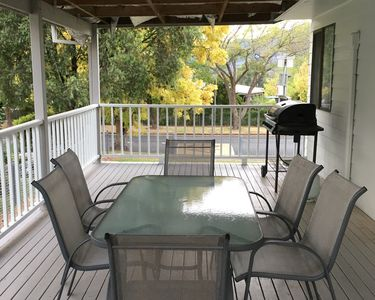 Deck with gas BBQ and outdoor dining setting.