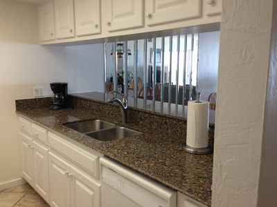 MODERN KITHEN WITH STAINLESS DOUBLE SINK AND GRANITE COUNTER TOPS.