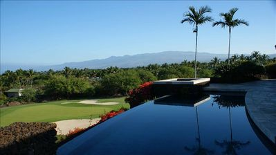 Infinity-edged pool boasts majestic views of the golf course, mountains & ocean