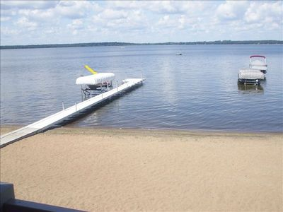 View overlooking beach, dock, water slide and rental boats.