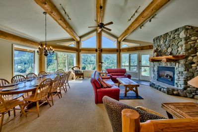 Large living area with dining table, panoramic views and river rock fireplace.