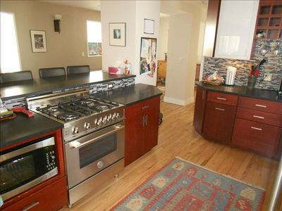 Gourmet kitchen with stainless appliances, glass backsplash, and cherry cabinets