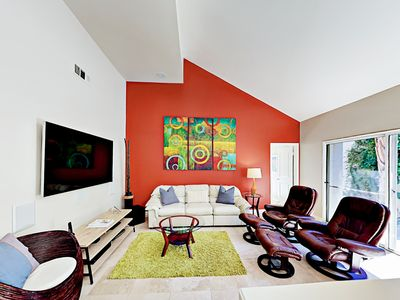 "TV Lounge - A stylish TV lounge features 2 recliner chairs with ottomans, a comfy sofa, and 60"" TV."