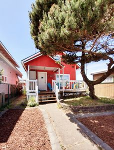 Front of house w/deck & adirondack chairs + fenced yard 4 kids & pups 2 play in!