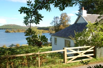 The side view of the Cottage down to the garden and Loch Knockie.