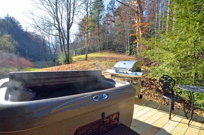 The steam rolling off the hot tub on the back deck with Grill and bistro table