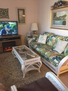 Electric fireplace in tropical décor living room. Queen size sofa bed