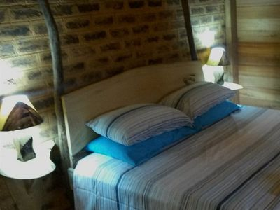 Handcrafted bed with rustic bedside tables and lamps