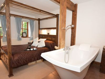 King- size bedroom with four poster and freestanding bath