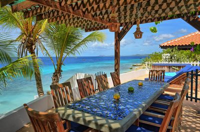 Dining table under the pergola at the seaside.