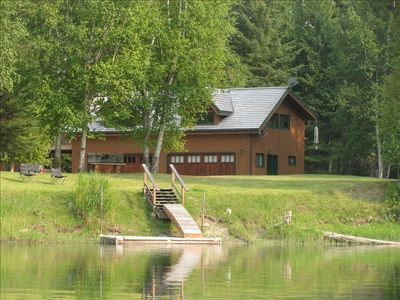 view from the kayak on the water - - boat dock, lawns and house