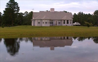 Back of house with barbecue grill and picnic table over looking pond