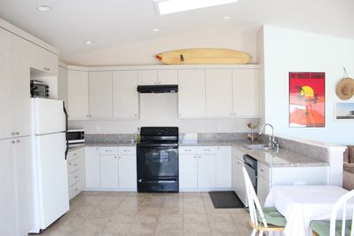 The spacious kitchen is fully-stocked with plates, glasses, cutlery, cookware.