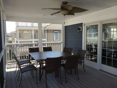 Large square dining table on the screened-in porch seats 8 comfortably.