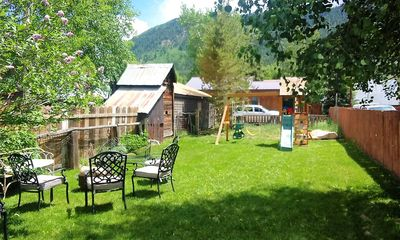 Large backyard equipped with loan chairs, firepit, grill and a nice playground.