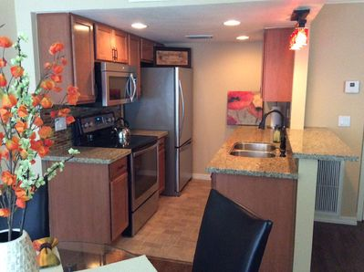 Newly updated open galley kitchen, stainless steel appliances, bar seating.
